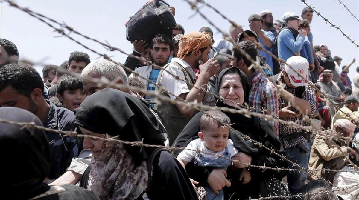 Refugiados sirios esperan cruzar desde su país la frontera que les separa de Turquía cerca de Akcakale en la provincia de Sanliurfa.