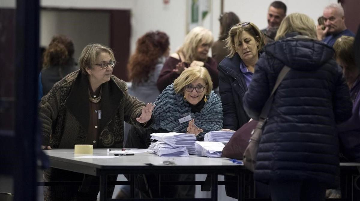 Miembros de una mesa electoral abren los sacos con las papeletas del referéndum.