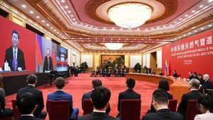 El presidente de Rusia, Vladimir Putin (pantalla del centro) dialoga con su homólogo chino, Xi Jinping, por videoconferencia en laceremonia de inauguración de un nuevogasoducto ruso a China.