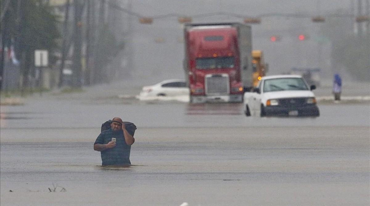Un hombre camina por una de las principales avenidas de Houston convertida en una río de agua.