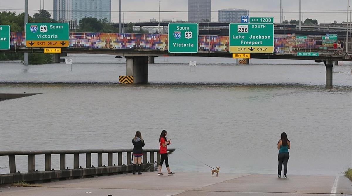 Residentes de Houston contemplan el nivel de agua que cubre parte de una autopista de entrada a Houston.