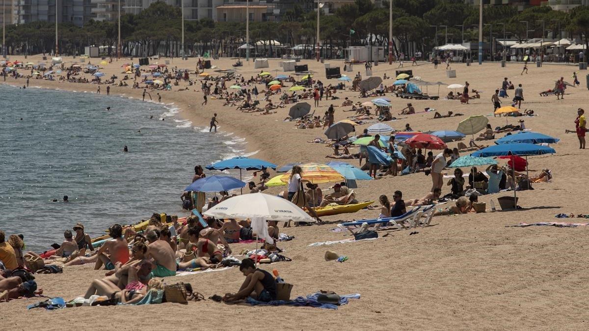Bañistas disfrutan del primer día de libertad de movimiento en la playa grande de Platja d'Aro, este sábado.