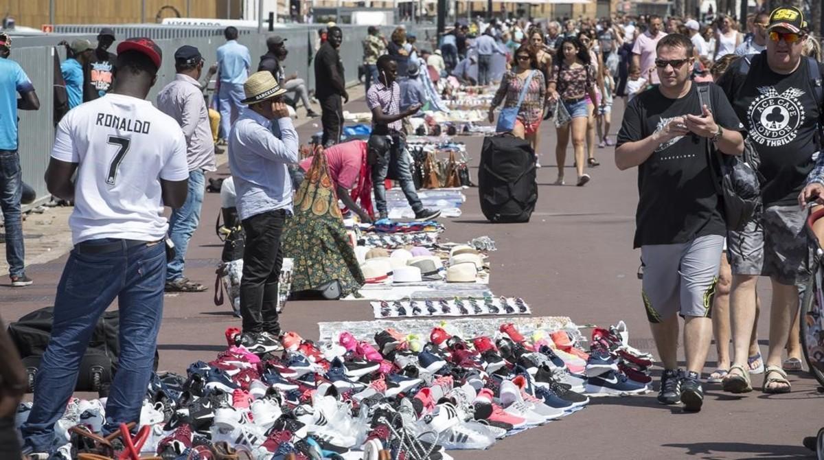 Un mantero, el viernes, en su puesto del Port Vell de Barcelona en el que vende zapatillas de deporte falsificadas de la marcas Adidas y Nike.