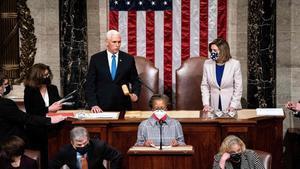 La presidenta de la Cámara de Representantes de EEUU., Nancy Pelosi (d), y el vicepresidente de Estados Unidos, Mike Pence tras retomar la sesión en el Congreso.