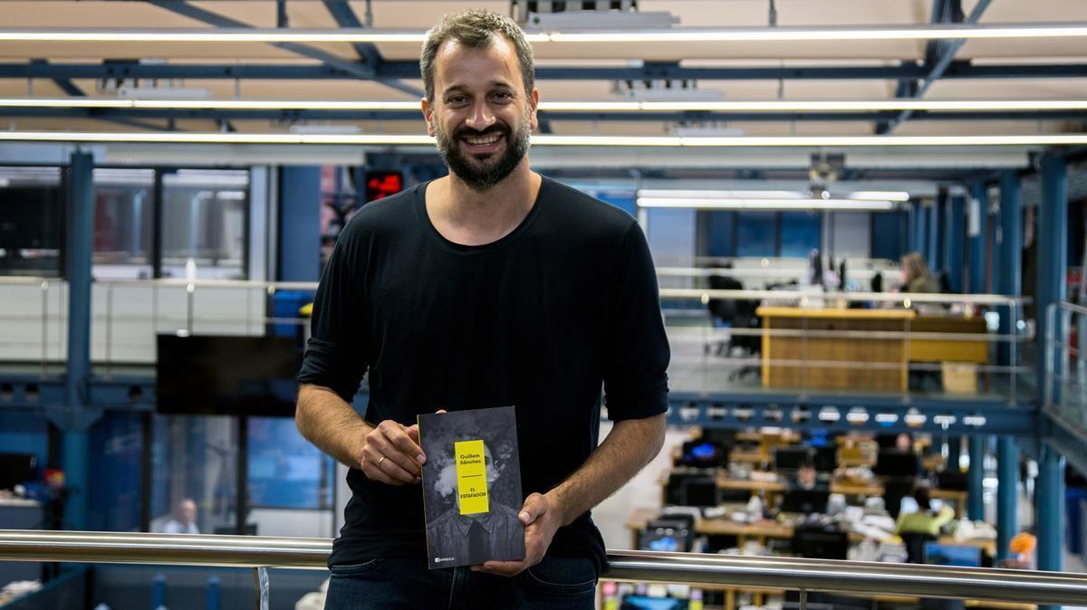 Guillem Sánchez posa en la redacción de EL PERIÓDICO con el iibro que publica, 'El estafador'.