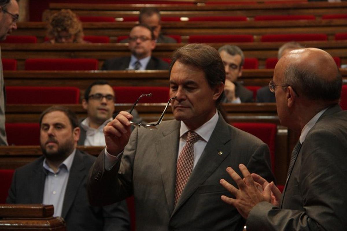 Artur Mas habla con el 'conseller' Boi Ruiz, con Oriol Junqueras al fondo, este jueves.