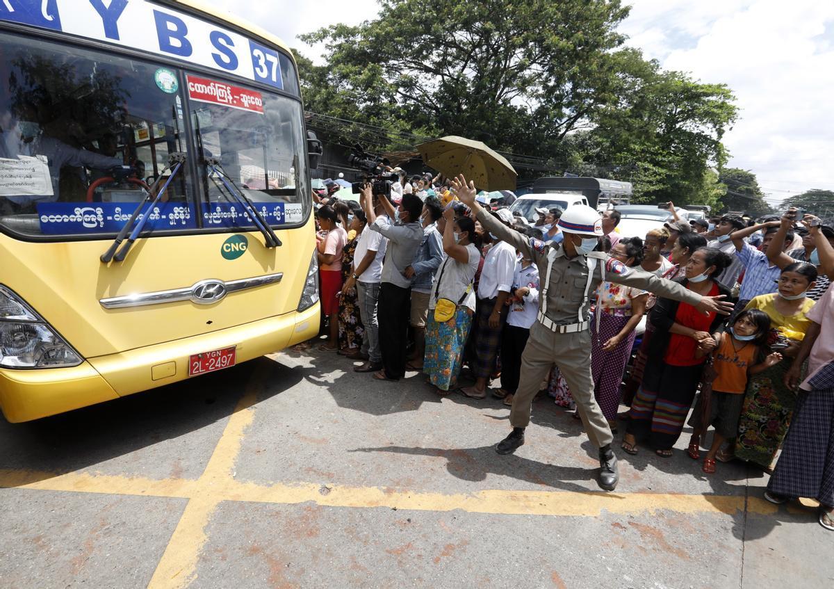 Un policía controla el tráfico ante la prisión Insein, en Yangon (Birmania), ante la salida de presos en autobús.