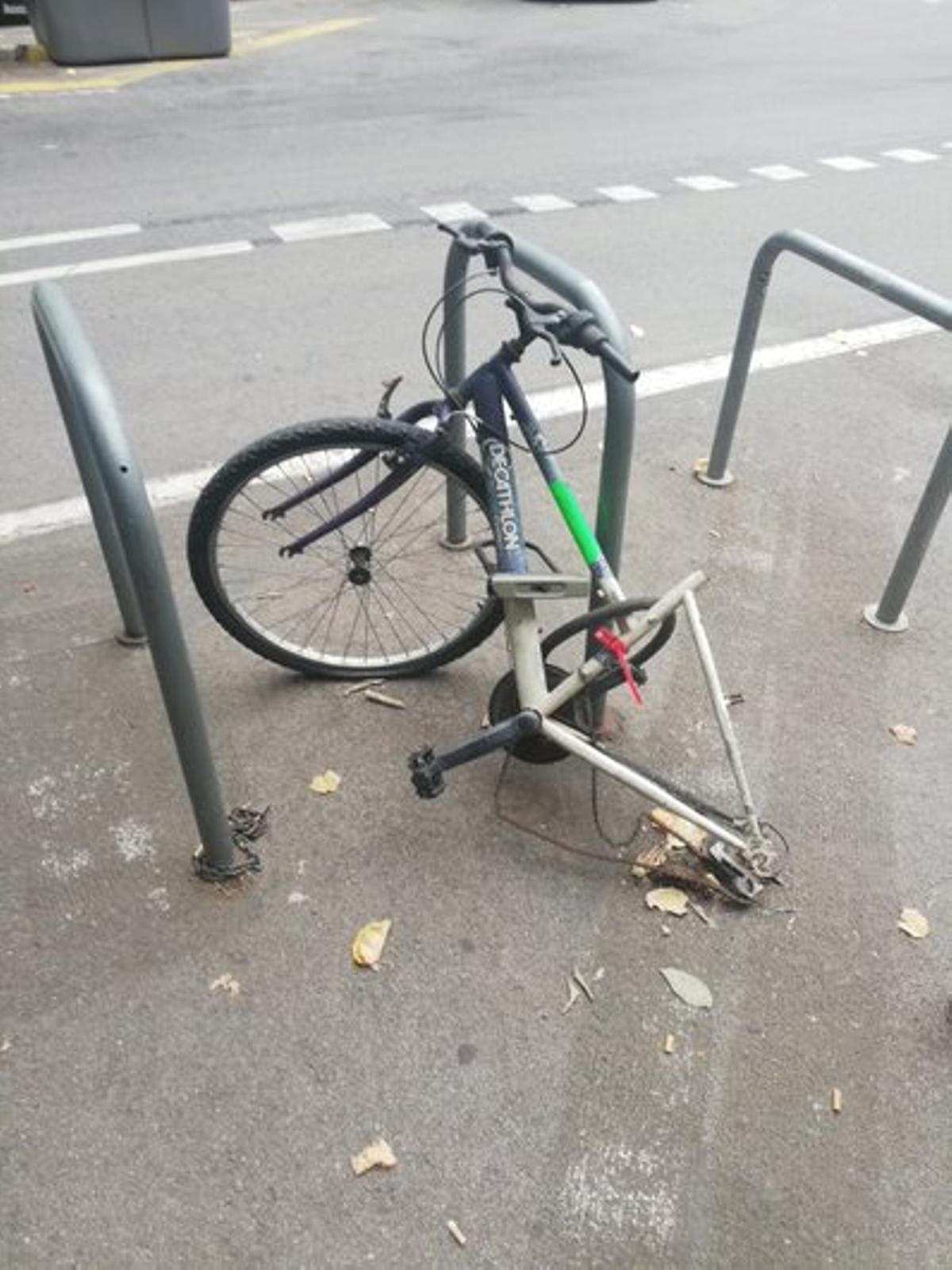 Bicicleta abandonada en el estacionamiento de bicis del chaflán (calle de Consell de Cent nº 122) con los adhesivos puestos y el precinto nº BT0015804.