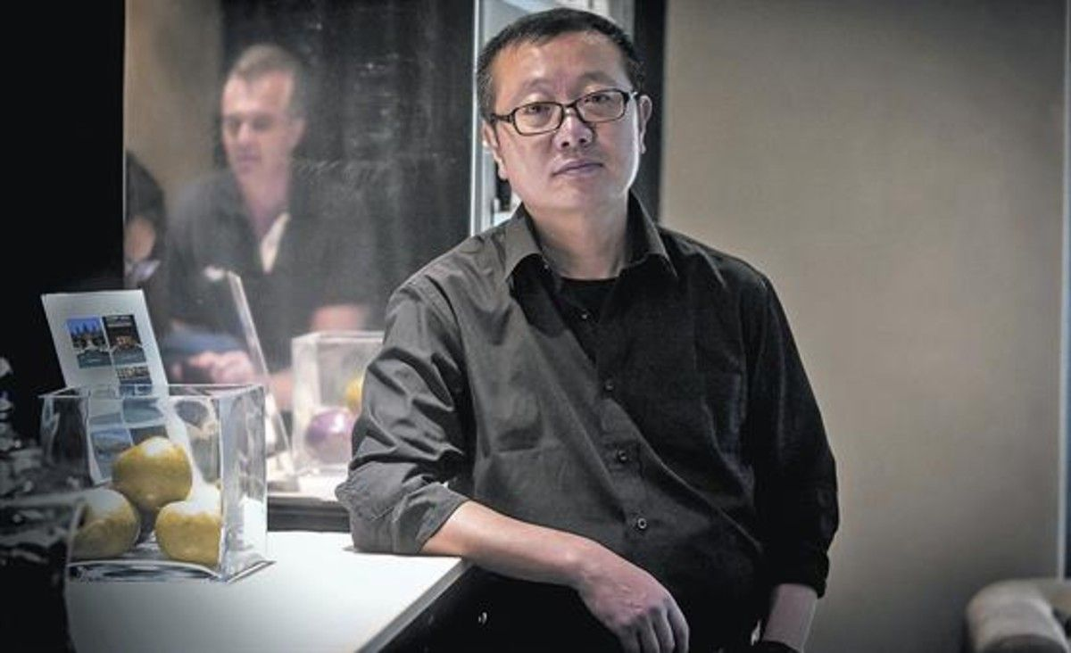 El escritor de ciencia ficción Liu Cixin posa en un céntrico hotel de Barcelona, el lunes. A la derecha, portada de 'El problema de los tres cuerpos' (Nova).