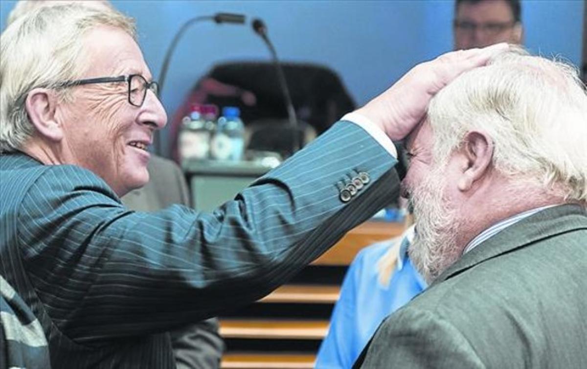 Juncker hace un gesto cariñoso hacia Cañete, ayer en Bruselas.