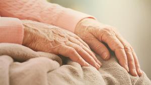 Las manos de una anciana sobre una manta.