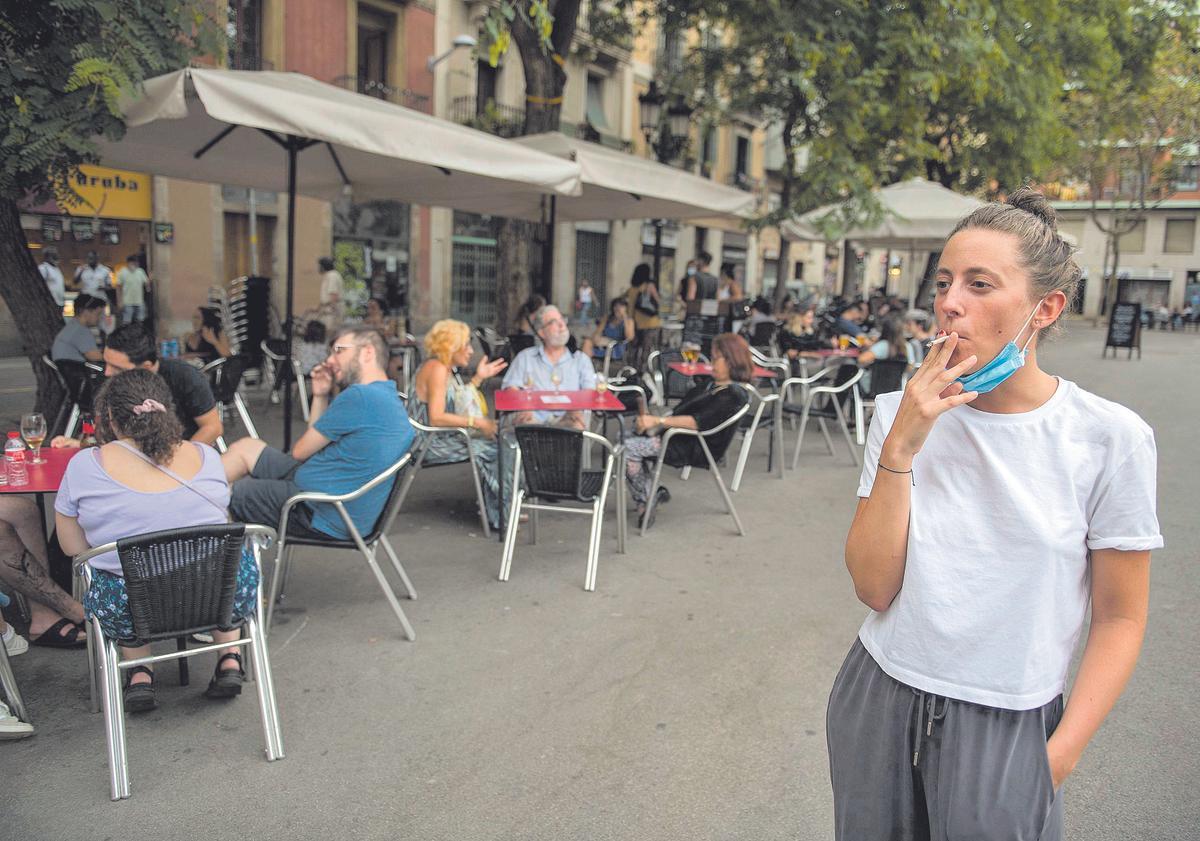 Una joven fuma al lado de una serie de terrazas, en Barcelona.