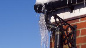 Cañería con hielo en el tejado de una casa.