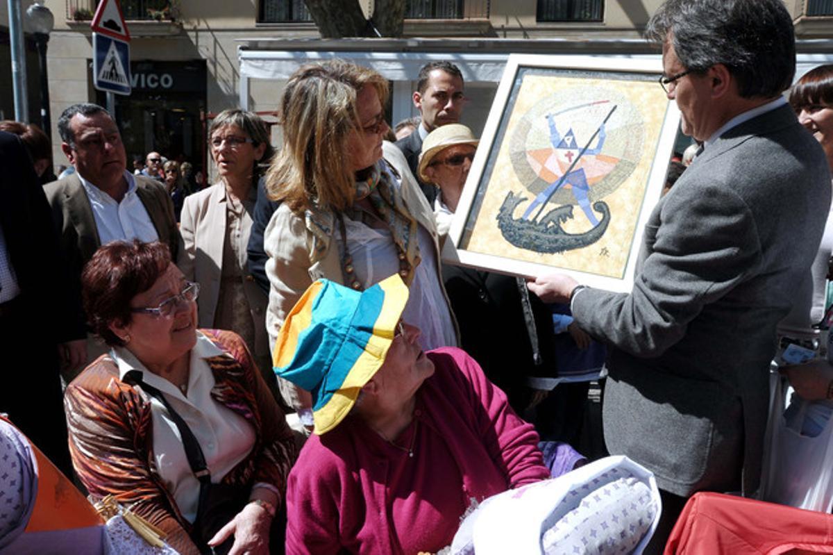 Artur Mas y su esposa contemplan el trabajo de una puntaire, este domingo, en Arenys de Mar.