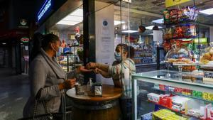 Una mujer compra un café en un local parcialmente abierto en Oporto (Portugal).