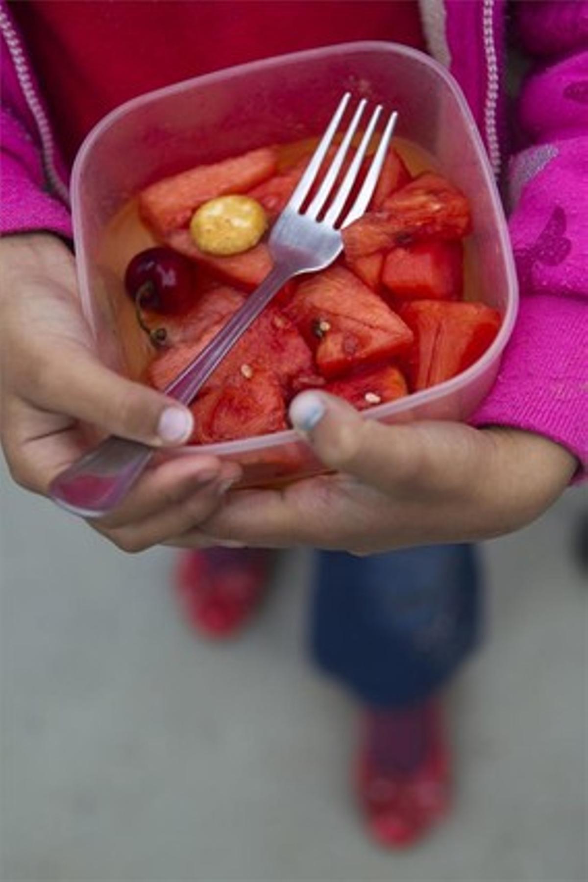 Un niño sostiene un plato de sandía.