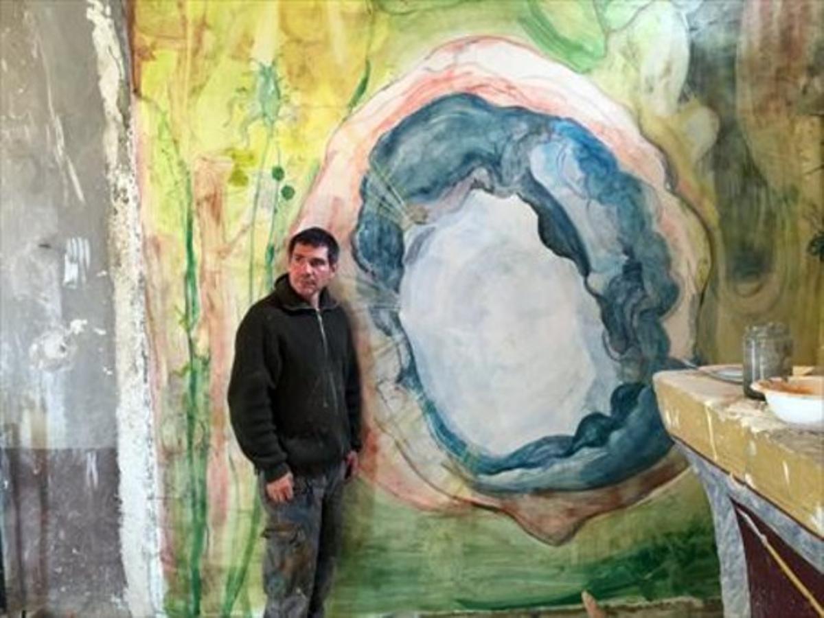 El artista Santi Moix, junto a uno de los frescos y coloristas murales que ha pintado en la iglesia Sant Víctor de Saurí del siglo XII.