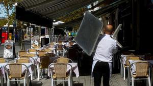 Un camarero recoge una mesa de una terraza de un restaurante del barrio de la Barceloneta.