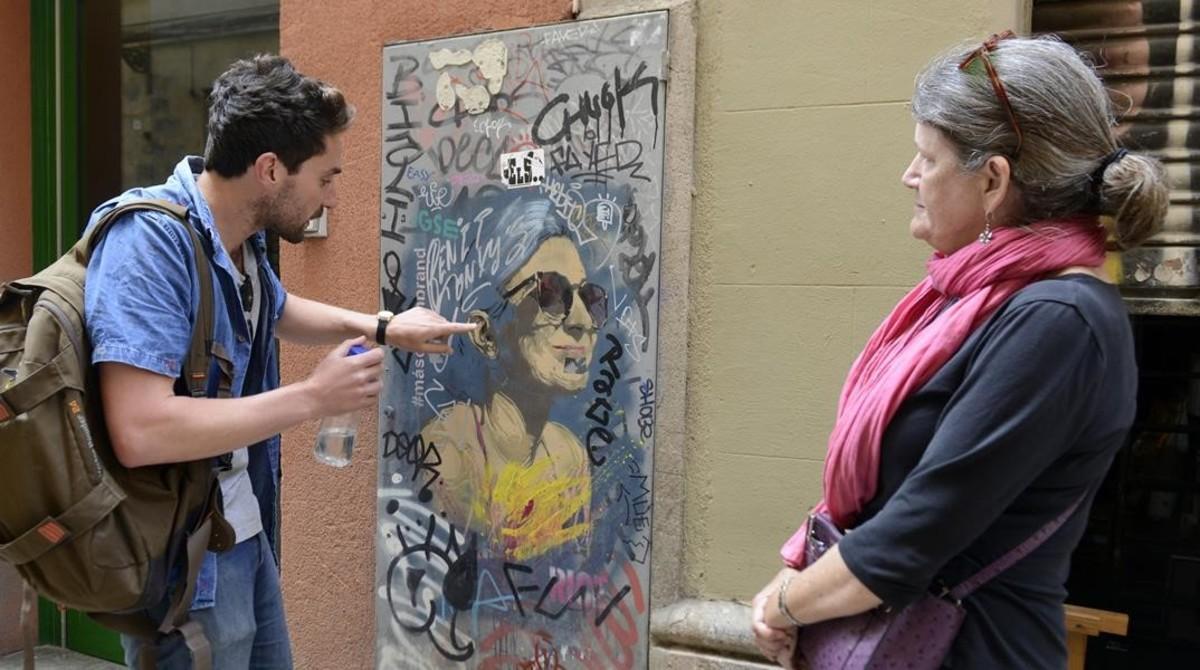 Dominic explica a Jane los detalles de un retrato grafiteado enla calle del Tiradors. Lo firma Rice.