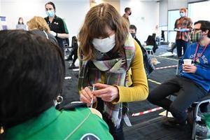 Una voluntaria aprende como administrar la vacuna en Canary Wharf.