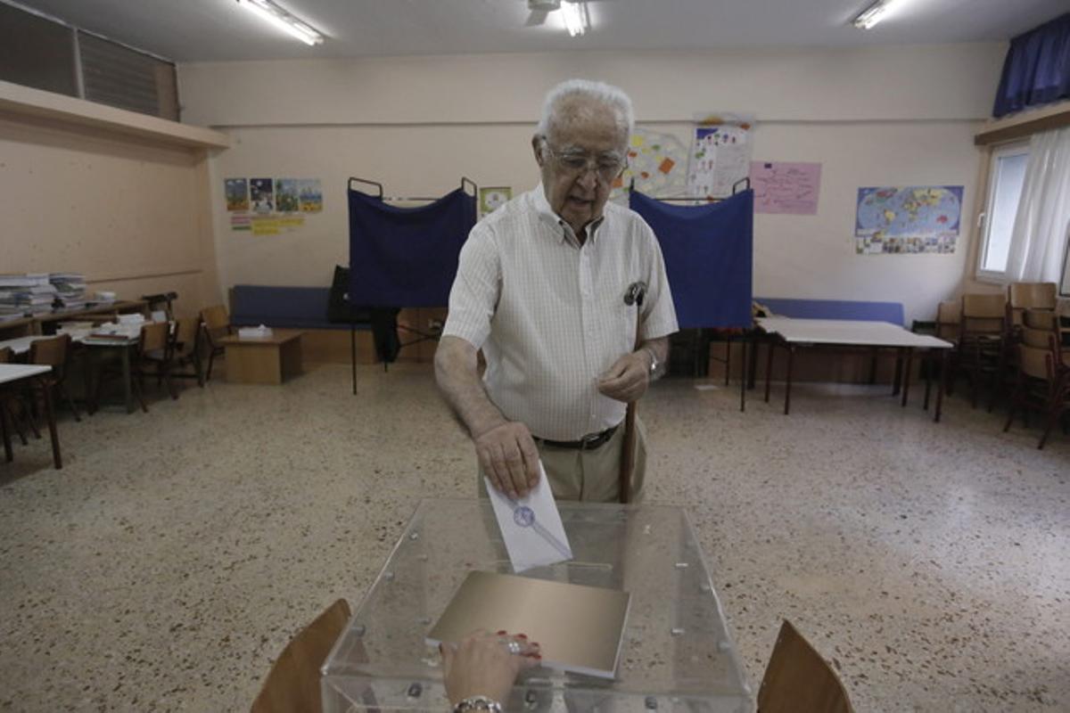 Un hombre deposita su voto en un colegio electoral de Atenas.