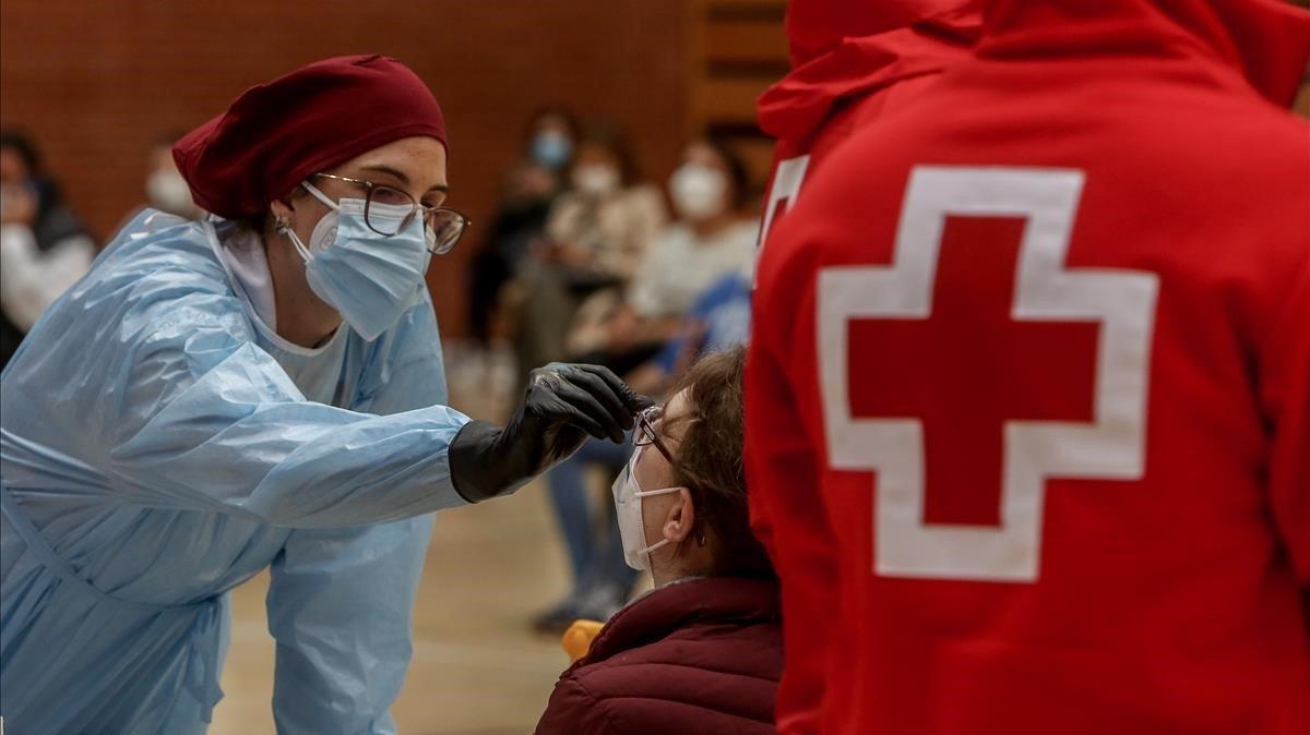 Una sanitaria realiza un test de antígenos para la detección del coronavirus a una mujer en el polideportivo municipal El Torreón, en Pozuelo de Alarcón (Madrid), este martes.