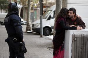 Dos okupas conversan ante la mirada de un agente, hoy, en Barcelona.
