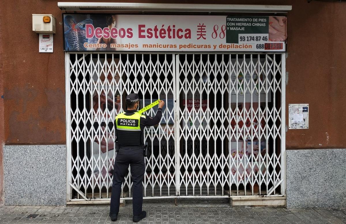 Un agente de la Policía Local de Mataró clausura un local de belleza de la ciudad.