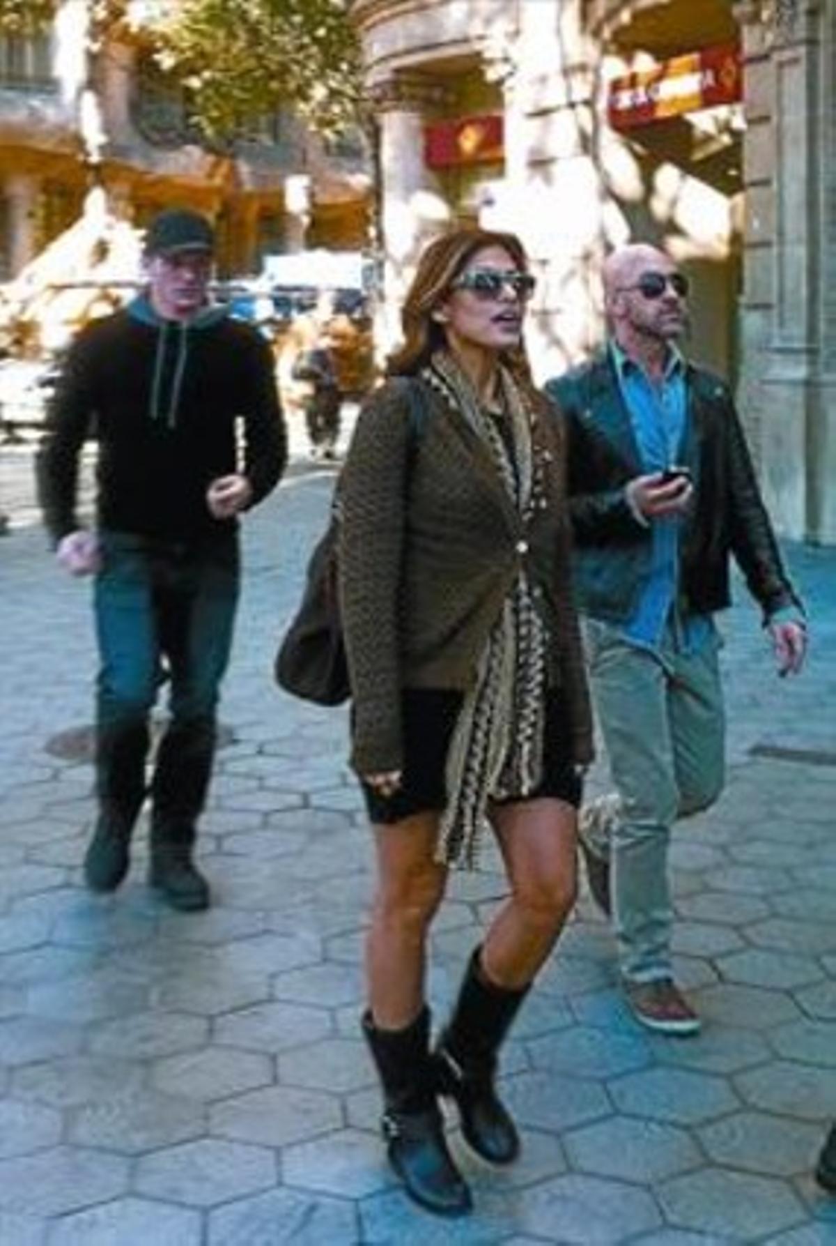 Eva Mendes, ayer, en el restaurante L'Escamarlà, a la hora de la comida. A la derecha, la actriz, en el paseo de Gràcia, justo a la altura de la Pedrera (a su espalda).