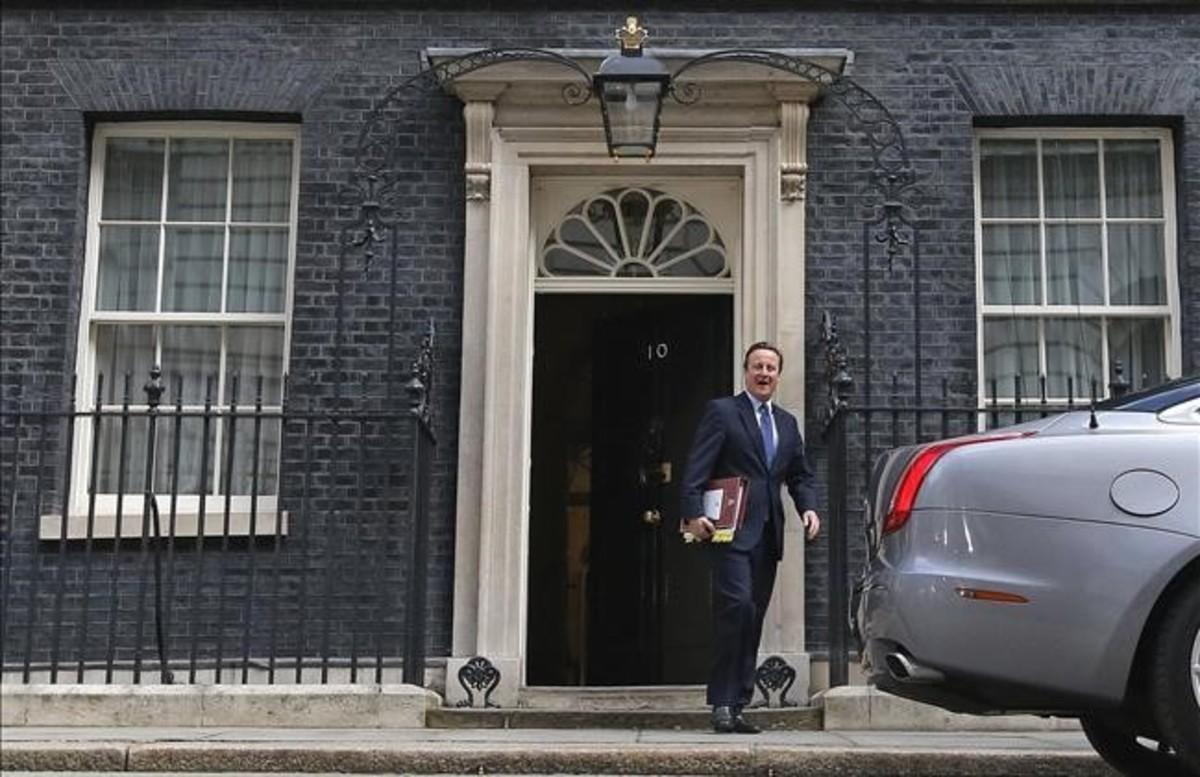 El primer ministro británico, David Cameron, sale de Downing Street para dirigirse a su última comparecencia en la Cámara de los Comunes.