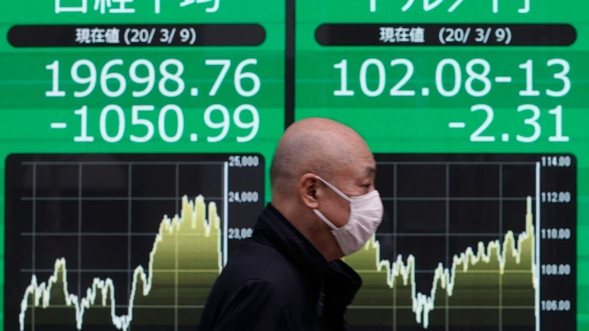El temor al avance del coronavirus causa un lunes negro en las bolsas asiáticas. En la foto, un ciudadano con mascarilla pasa frente a un cartel con información del índice Nikkei, en Tokio.
