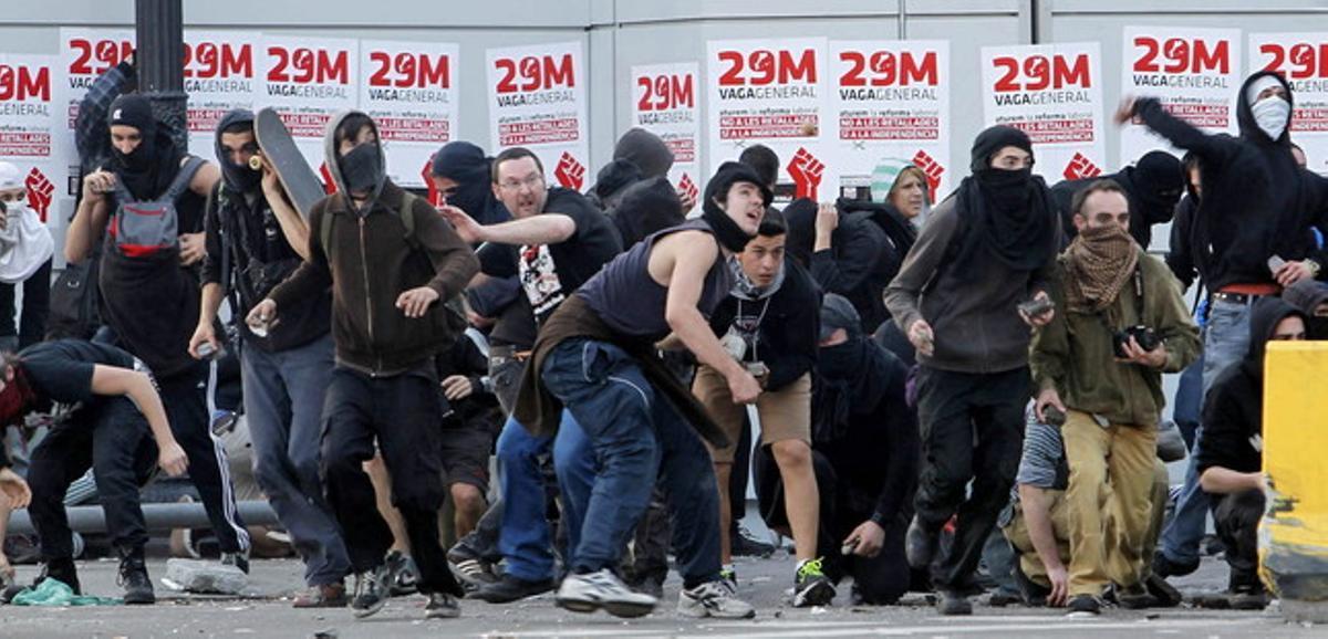 Manifestantes lanzan objetos a la policía durante los disturbios en la jornada de huelga.