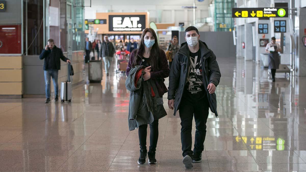 Ya hay siete pacientes más en España contagiados con el coronavirus. En la foto, pasajeros con mascarillas en el aeropuerto de El Prat.