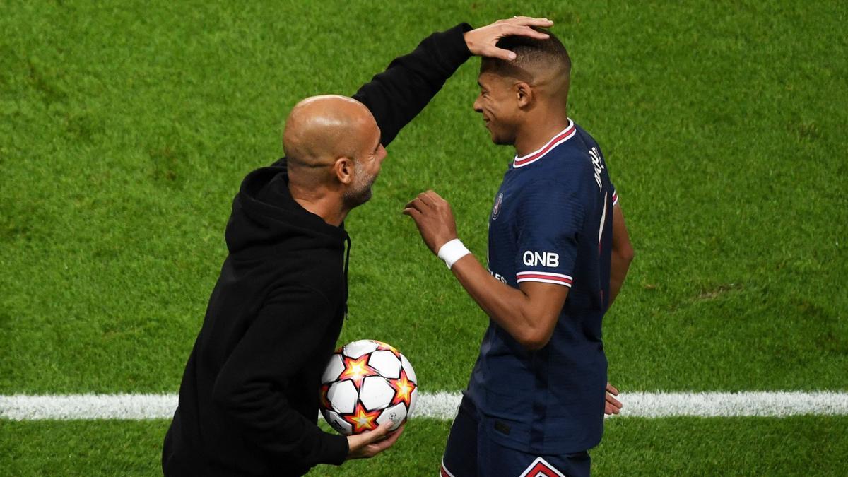 Pep Guardiola (L), hace un gesto con el delantero francés del Paris Saint-Germain, Kylian Mbappé.