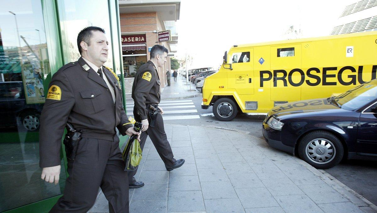 Dos vigilantes de seguridad de la empresa Prosegur camino a un furgón blindado.