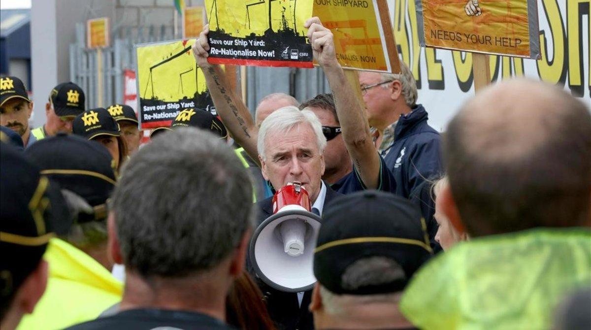 John McDonnell, del partido Laborista, habla con los trabajadores de los astilleros de Harland y Wolff que protestan por la salvación del astillero en Belfast, Escocia, en agosto de 2019