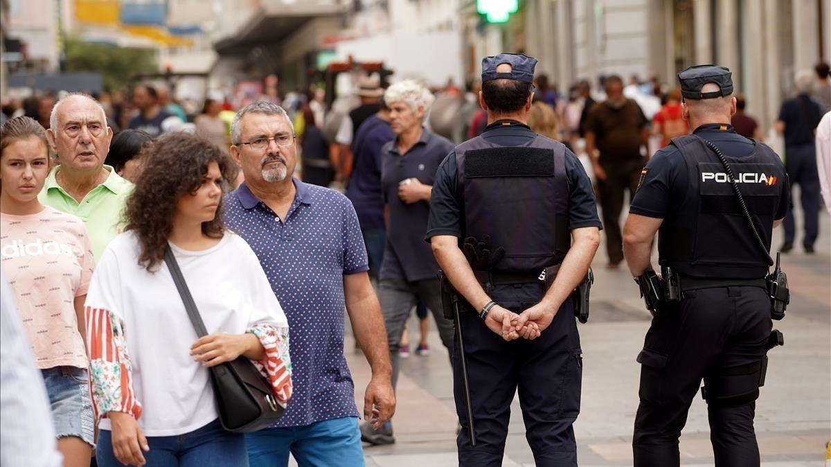 Dos policías nacionales patrullan por la calle Preciados, eje comercial y turístico del centro de Madrid.