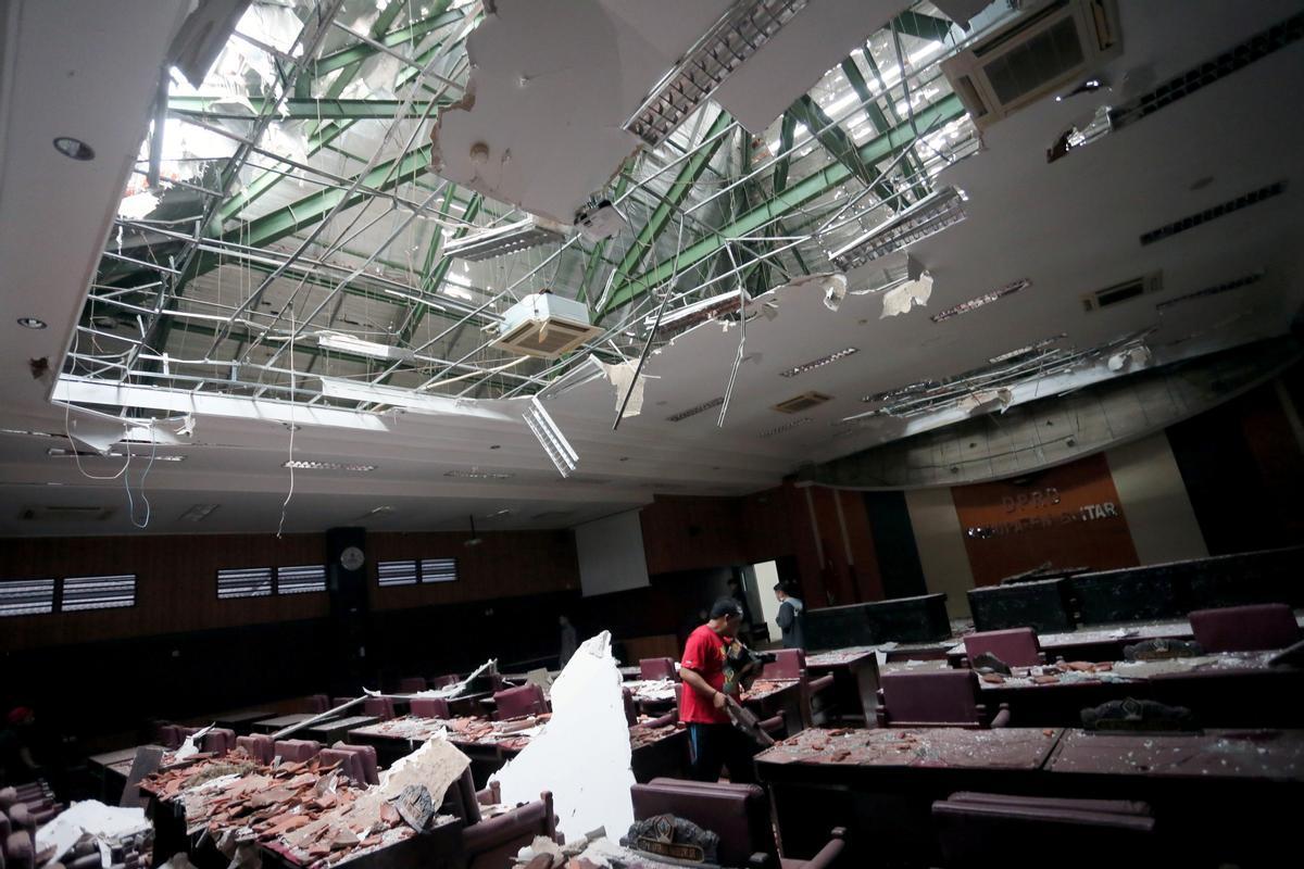 Un hombre recoge los trozos de un edificio dañado por el terremoto en Indonesia