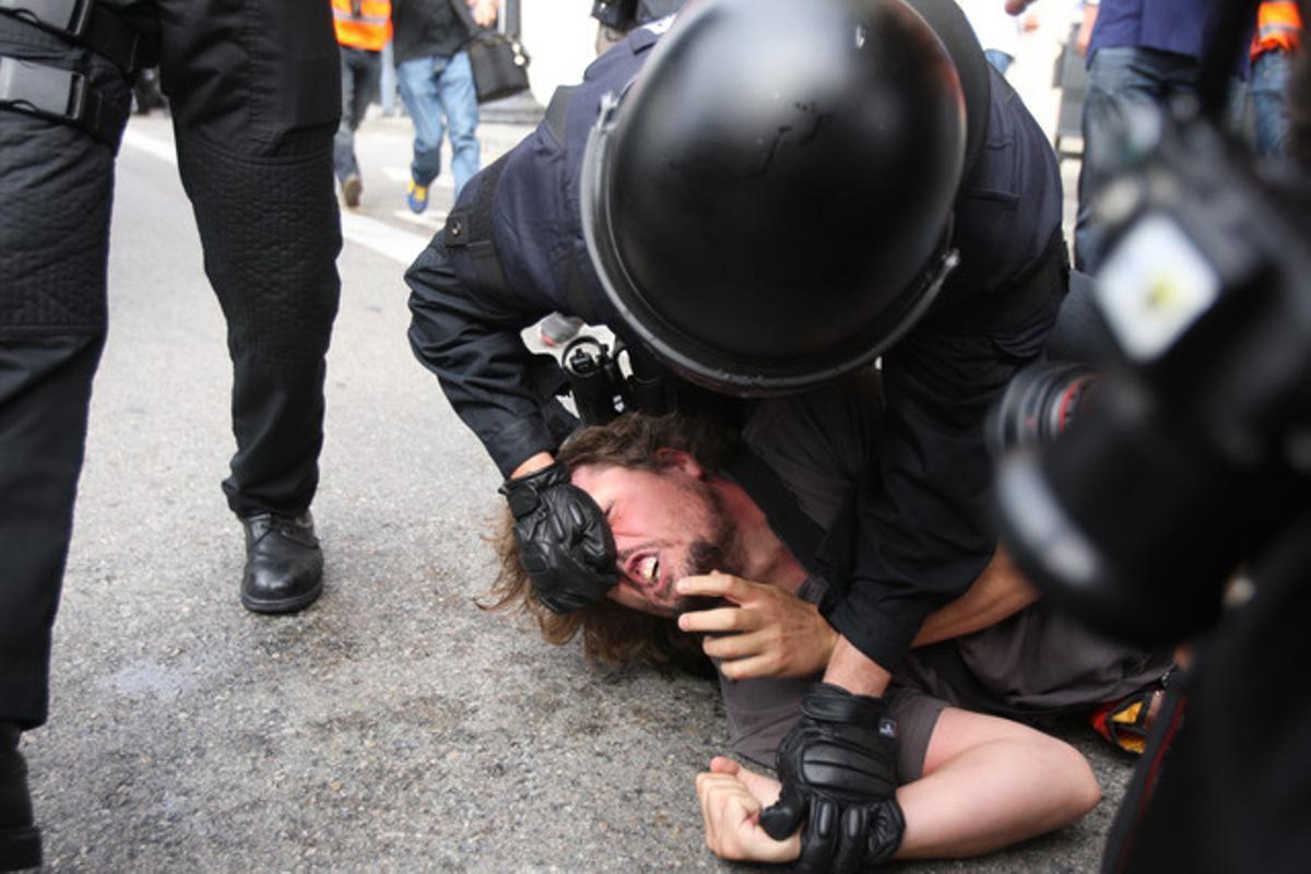 Un agente inmoviliza a uno de los ocupantes de la plaza de Catalunya de Barcelona, el 27 de mayo del 2011.