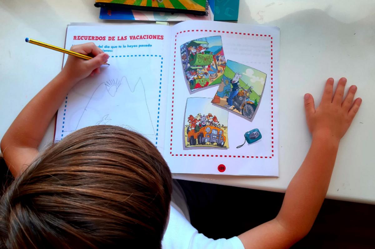 Un niño comenta los recuerdos de sus vacaciones en un cuaderno de verano