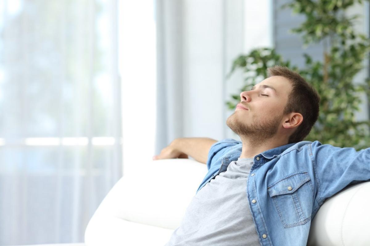 Un chico en silencio en el sofá con los ojos cerrados.