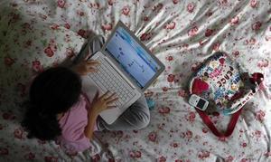 Una niña navega por internet desde su ordenador.