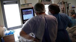Dos trabajadores del hospital Melun-Senart, cerca de París, miran el monitor de un paciente de covid-19 ingresado en la uci.