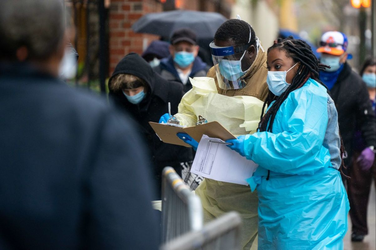 NEW YORK, NY - APRIL 24: Medical workers assist people standing in line at NYC Health + Hospitals/Gotham Health, Gouverneur waiting to be tested for the coronavirus (COVID-19) on April 24, 2020, in New York City. The NYC Health + Hospitals/Gotham Health, Gouverneur is one of the newest sites specifically for NYCHA city housing residents to open for diagnostic testing in some of the hardest-hit areas in New York City.   David Dee Delgado/Getty Images/AFP