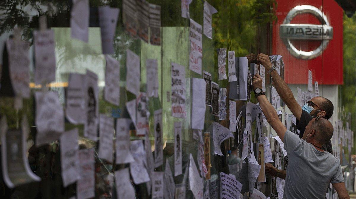Trabajadores de Nissan pegan carteles contra el cierre de la planta de la Zona Franca en el escaparate de un concesionario de la marca en Barcelona, el viernes 29 de mayo.