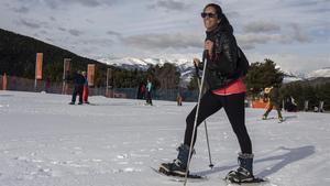 Una aficionada camina con raquetas de nieve por las pistas de La Molina.