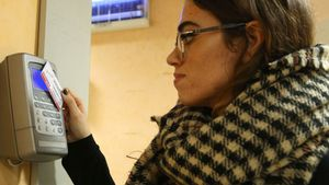 Una trabajadora ficha en un aparato de control horario al empezar su jornada laboral.