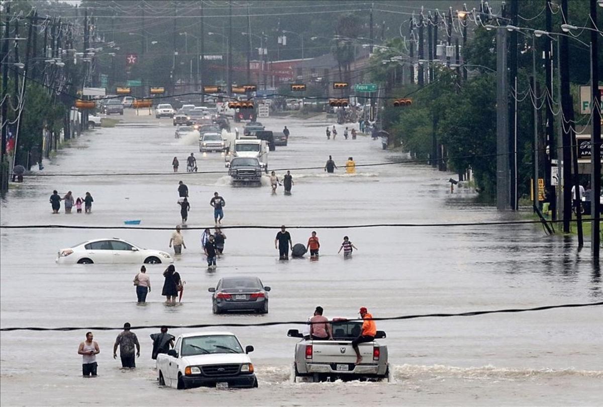 Vecinos de Houston caminan por una de las principales arterias inundadasde la ciudad.