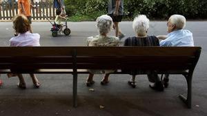 Un grupo de ancianos descansan en un banco en un parque de Barcelona.