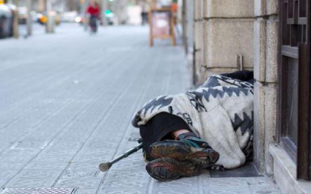Una persona sin hogar duerme en una calle de la capital catalana.
